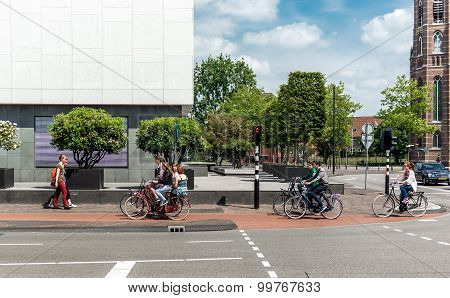Eindhoven, Netherlands- May 24, 2015: People Crossing The Street By Bicycle. Bicycles Are Popular Wa