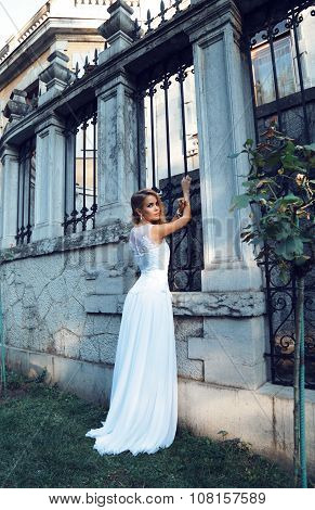 fashion outdoor photo of beautiful woman with blond hair wears elegant wedding dressposing beside antic villa stock photo