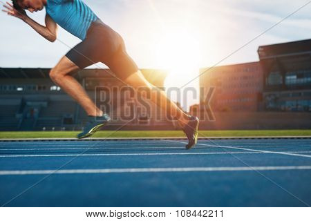 Shot of young male athlete launching off the start line in a race. Runner running on racetrack in athletics stadium. ** Note: Soft Focus at 100%, best at smaller sizes stock photo