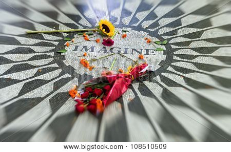 Selective Focus of Rose Bouquet and Flowers Strewn Across Surface of John Lennon Imagine Mosaic in Memorium, Strawberry Fields Area of Central Park, New York City, New York, USA stock photo