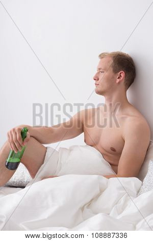 Young man is sitting in a bed and drinking beer stock photo