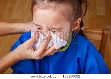 Parent hand helping the playing little girl to blow her nose with a hygienic wet wipe. Seasonal sickness. stock photo