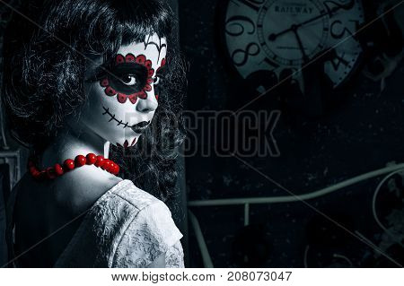 Little girl with santa muerte makeup for halloween is standing in left of the photo looking over her shoulder. Girl has black curly hair white dress and red bead