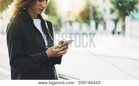 Girl holding smart phone on background sun atmospheric city and bike hipster using in female hands and texting mobile street lifestyle and flare sun tourist planing route in summer gadget concept stock photo