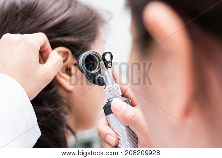 Doctor examined the patient's ear with Otoscope. Patient seem to have problems with hearing.
