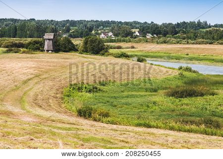 Rural Russian summer landscape with old wooden windmill on the coast of Sorot river. Mikhaylovskoye Pushkinogorsky District of Pskov Oblast Russia stock photo