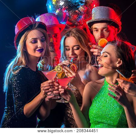 Cocktail party with group people dancing and drink cocktail. Happy women in evening dresses and men have fun in night club and disco ball background. Rest after a hard day at work. stock photo