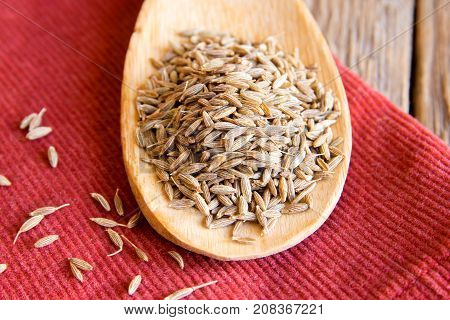 cumin seeds on wooden spoon over red napkin close up stock photo