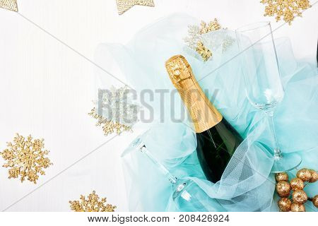 Bottle of a champagne and glasses. Celebration Flat lay. White wooden background turquoise tulle golden berries and snowflake stock photo