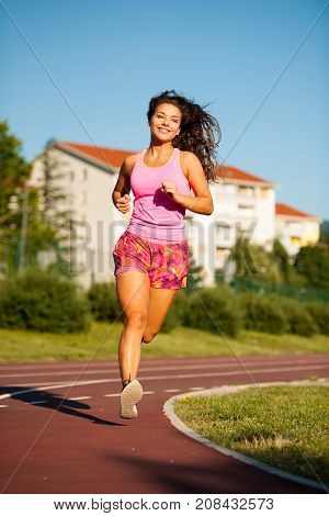 active young woman runs on atheltic track on summer afternoon stock photo