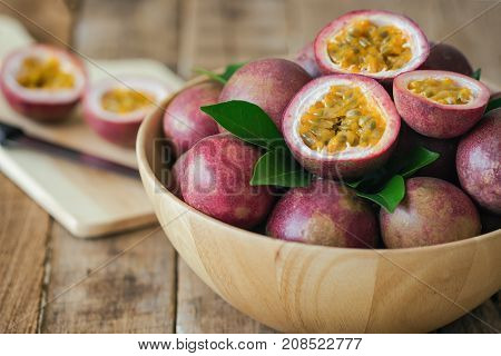 Passion fruit on wood bowl put on wood table in side view for background or wallpaper. Prepare passion fruit on cutting board for homemade dessert or cooking. Ripe passion fruit so sweet and sour. Fresh passion fruit background concept. stock photo