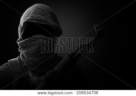 Blurry Background of Terrorist carry weapon hidden in darkness. terrorism concept. on black background with dim light. Black and White. stock photo