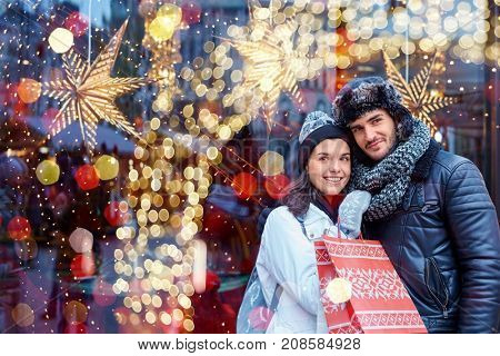 Christmas shopping together. Young happy couple doing christmas shopping. Christmas lights in the ba