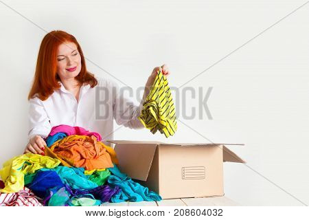 The girl chooses extra things that would throw them away. A box for charity. stock photo