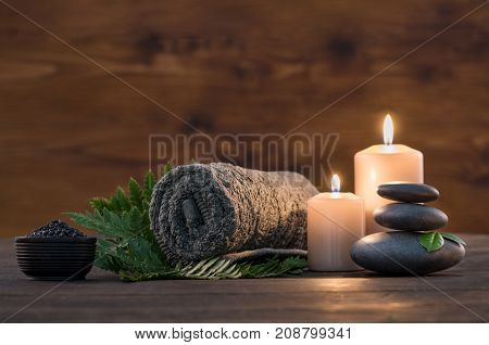 Towel on fern with candles and black hot stone on wooden background. Hot stone massage setting lit b
