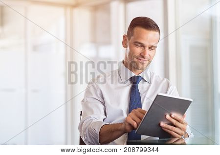 Smiling businessman using digital tablet at work. Portrait of a happy formal man working on computer