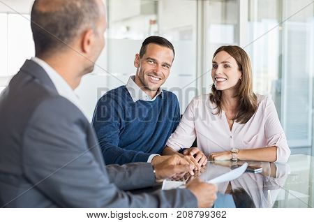 Mature financial advisor showing report to young couple for their investment. Salesman and positive