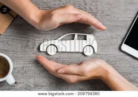 Hands protecting icon of car over wooden table. Top view of hands showing gesture of protecting car.