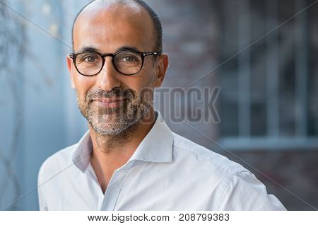 Portrait of happy mature man wearing spectacles and looking at camera outdoor. Man with beard and gl
