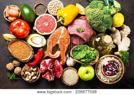 Balanced diet food background. Organic food for healthy nutrition superfoods. Meat fish legumes nuts seeds greens oil and vegetables. Top view on dark stone table.