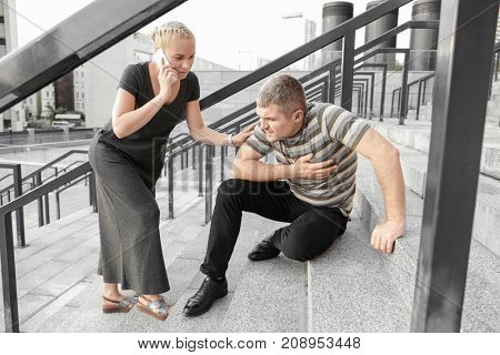 Woman calling ambulance for man suffering from heart attack outdoors stock photo