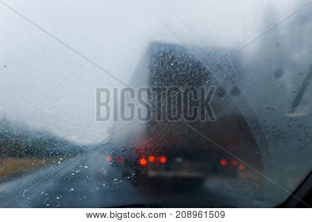 Rain drops on windscreen and blurred truck in forest road. Overtaking of the truck. Low visibility. Concept of road danger bad weather. stock photo