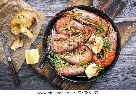 Traditional fried black tiger prawn with garlic bread as top view in a black frying pan  stock photo