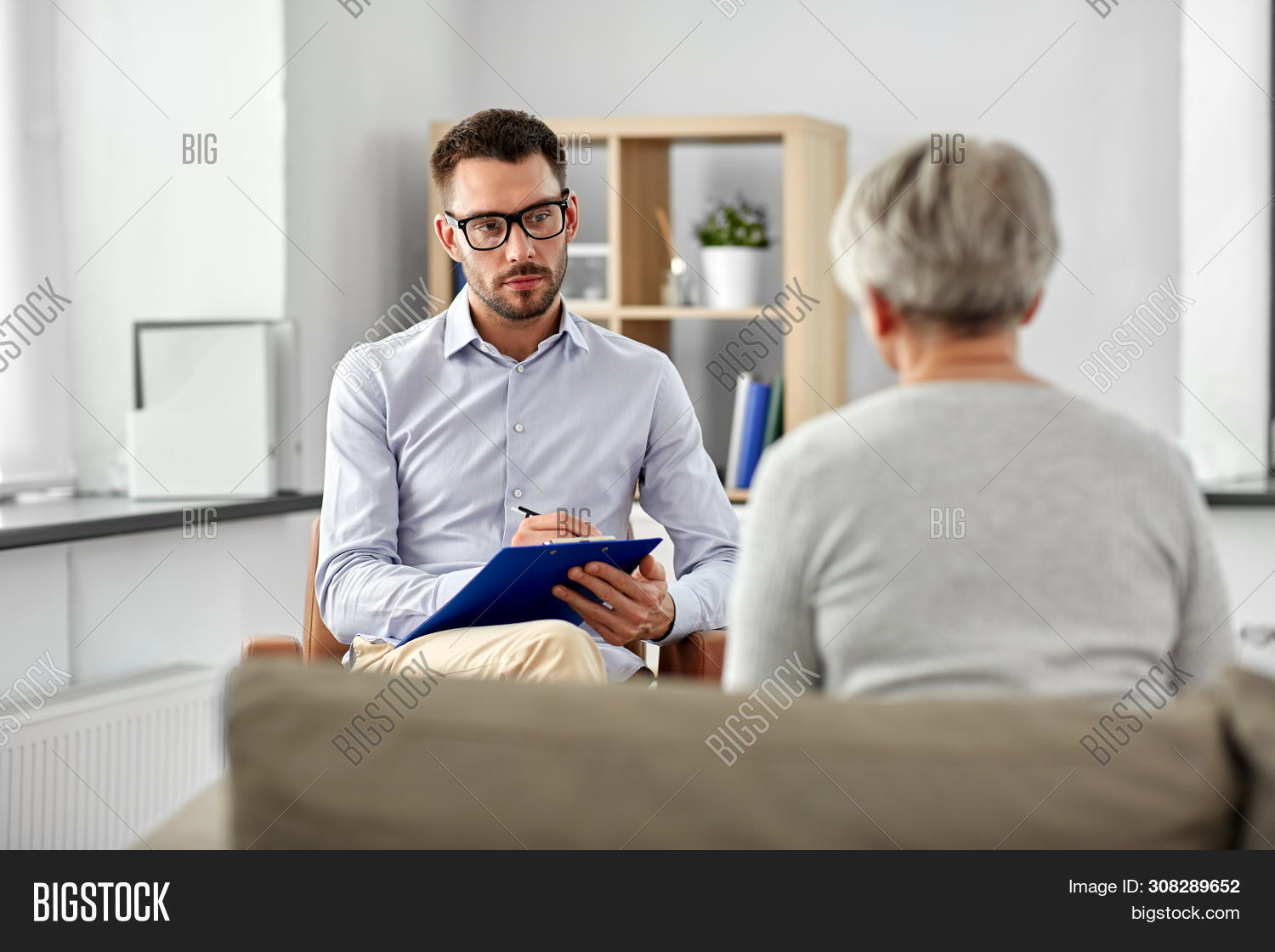 geriatric psychology, mental therapy and old age concept - psychologist with clipboard taking notes and listening to senior woman patient at psychotherapy session