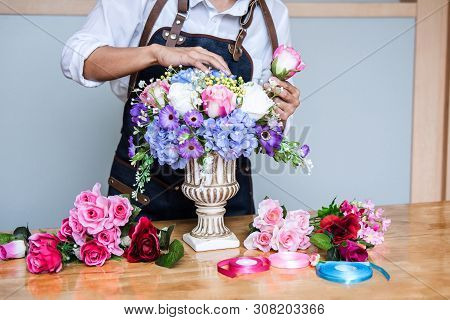 Arranging artificial flowers vest decoration at home, Young woman florist work making organizing diy artificial flower, craft and hand made concept. stock photo