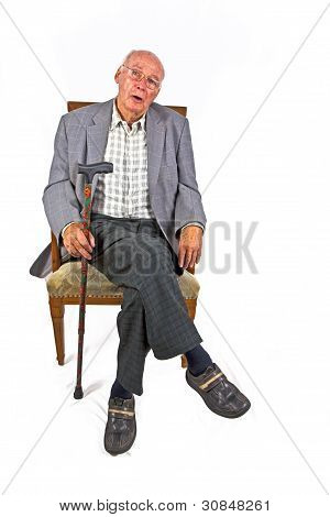 old man sitting in the armchair and looks very confident and happy stock photo