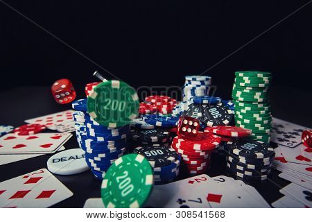 Close Up Stack Of Different Colored Poker Chips, Playing Cards And Dices Isolated Over Black Casino