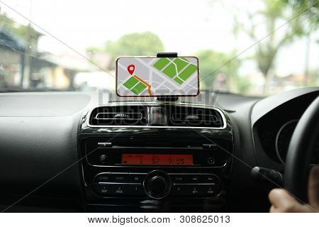 Car driver using smart phone with GPS map navigation while driving, car sharing app concept stock photo