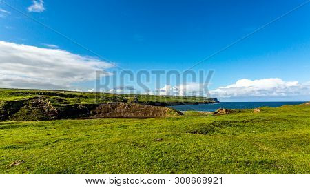View of a meadow green next to Doolin Bay with the cliff in the background, Wild Atlantic Way, Irish landscape on a beautiful sunny spring day on a calm day in County Clare in Ireland stock photo