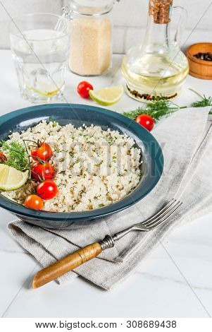 Light dietary food, couscous with tomatoes, lime and fresh herbs in dark bowl, white marble background stock photo