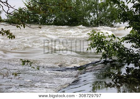 Fast flowing muddy flood water going over temporary sandbags flood protection wall covered with thick black nylon and surrounded with small trees on rainy spring day stock photo