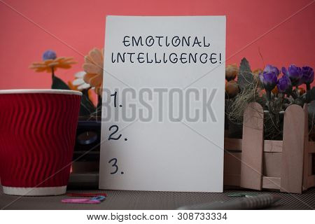 Handwriting text writing Emotional Intelligence. Concept meaning Self and Social Awareness Handle relationships well Flowers and stationary plus plain sheet with paper big cup above a table. stock photo