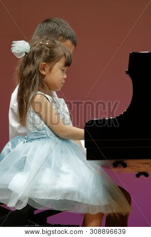 Japanese brother and sister playing piano on stage (9 years old boy and 4 years old girl) stock photo
