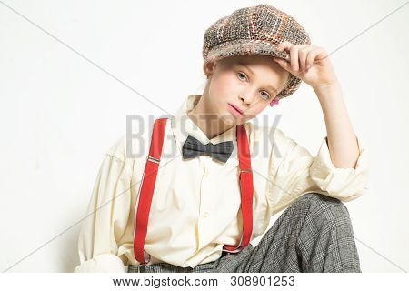 Confident in her style. teen girl in retro suit. suspender and bow tie. old fashioned child in checkered beret. vintage english style. jazz step fashion. retro fashion model. vintage charleston party. stock photo
