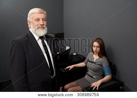 Front view of elder man wearing smart suit looking at camera and smiling during lie test. Male working with lie detector and checking truth. Professional worker using polygraphs and modern technology. stock photo