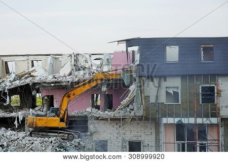 A yellow excavator demolishes a multi-storey building with a ladle. Technique destroys the building, is fittings, concrete and stones. Destroyed house, broken floors, destroyed the walls and roof. stock photo