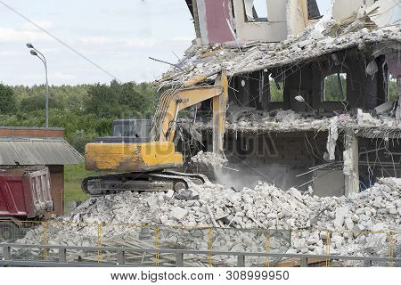 Yellow excavator picks up construction waste for loading onto a truck. Technique destroyed the building, is reinforcement, concrete and stones. Destroyed house, concrete, fittings, dust flies. stock photo