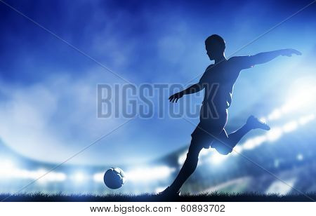 Football, soccer match. A player shooting on objective. Lights on the stadium during the evening.
