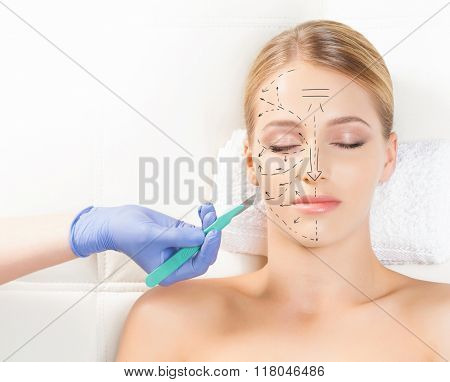 Beautiful woman getting face lifting operation. Drawing arrows and a scalpel over her face. Aging and plastic surgery concept. stock photo