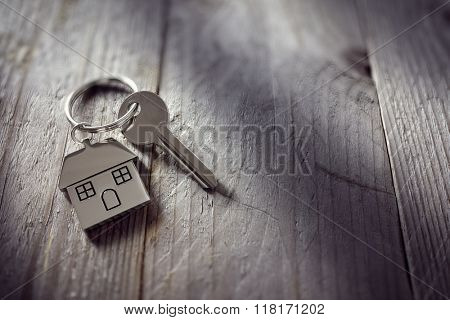 House key on a house shaped keychain resting on wooden floorboards concept for real estate, moving home or renting property stock photo
