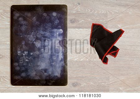 Black microfiber cloth ready to wipe finger prints and general dust and dirt on screen of touchscreen tablet or smartphone on wooden desk stock photo
