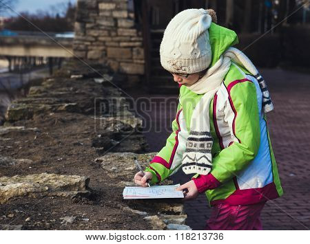 Girl baby girl drawing in the albumin autumn park stock photo