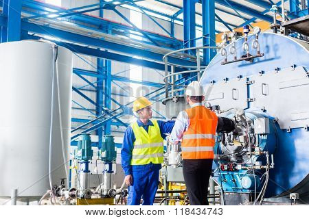 Worker and manager in industrial factory discussing acceptance of machine