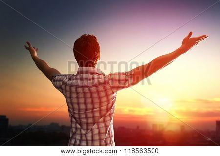 Successful man looking up to sunset sky celebrating enjoying freedom. Positive human emotion feeling