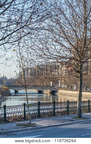 Bucharest Romania - January 10: Dambovita River on January 10 2016 in Bucharest. Vertical view of winter cityscape with frozen trees buildings river and bridge. stock photo
