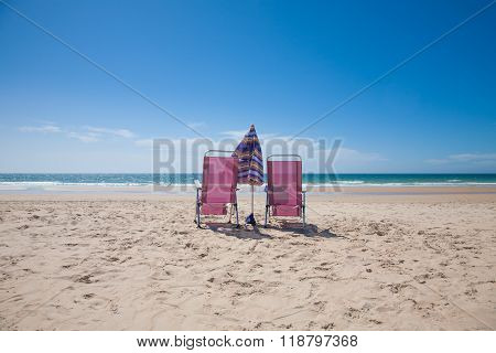 two lonely purple metal back seat beach chairs and umbrella parasol closed on sand at Vejer Palmar Beach with horizon blue clean sky in Cadiz Andalusia Spain stock photo